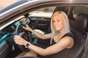 Attractive blonde female driver, without sunglasses, in the driver seat of our stretch limo in Phoenix