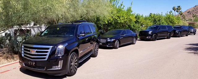 Several of our SUVs and sedans in a row one behind the other along the side of a street. Part of our Phoenix Limo Service fleet.